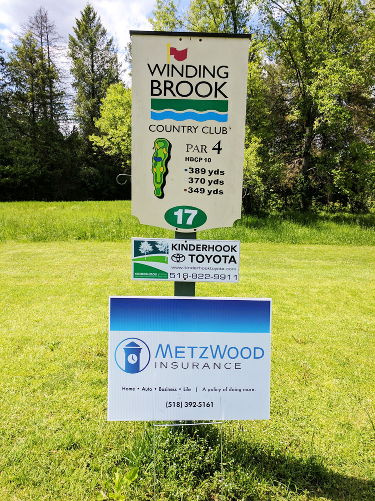 Sponsor signs for Kinderhook Toyota and Metzwood Insurance at Iron Horse Cigar Depot charity golf tournament